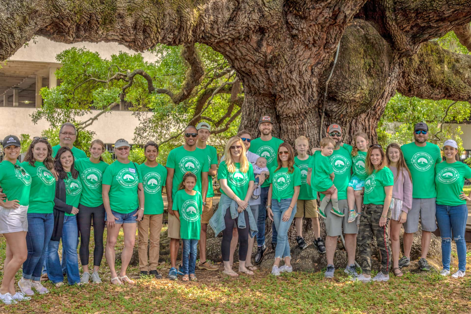 group of people matching shirts under tree