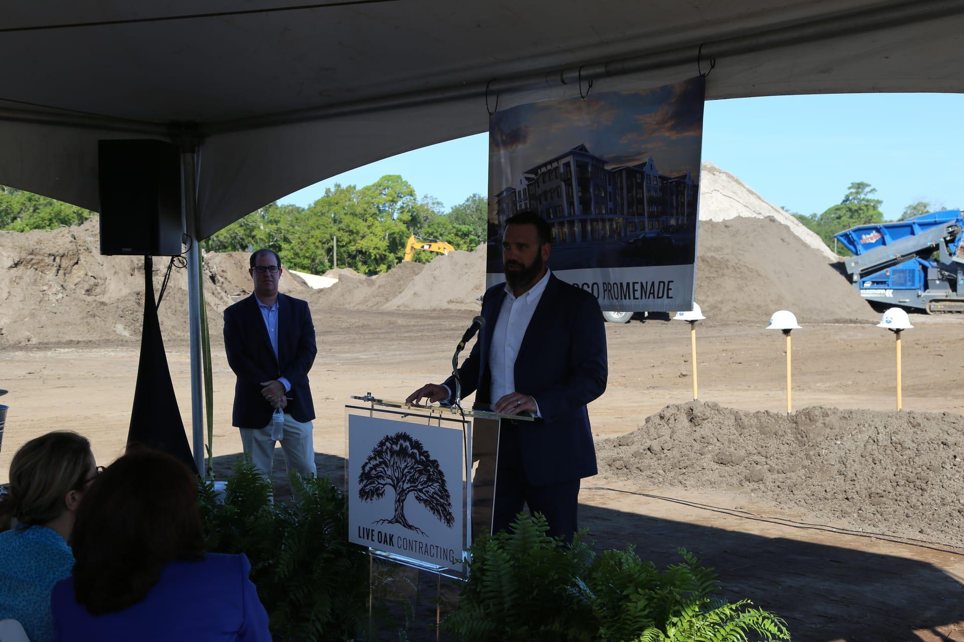 man speaking at podium at construction site
