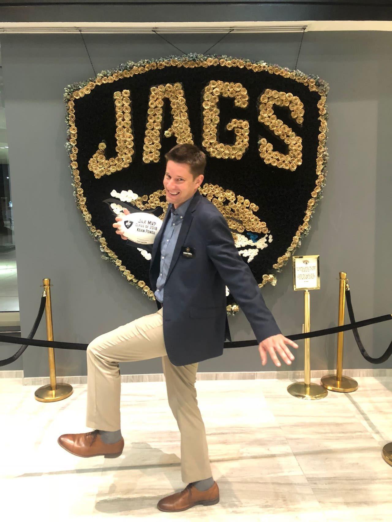 happy man holding football jacksonville jaguars