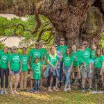group under tree outside matching shirts