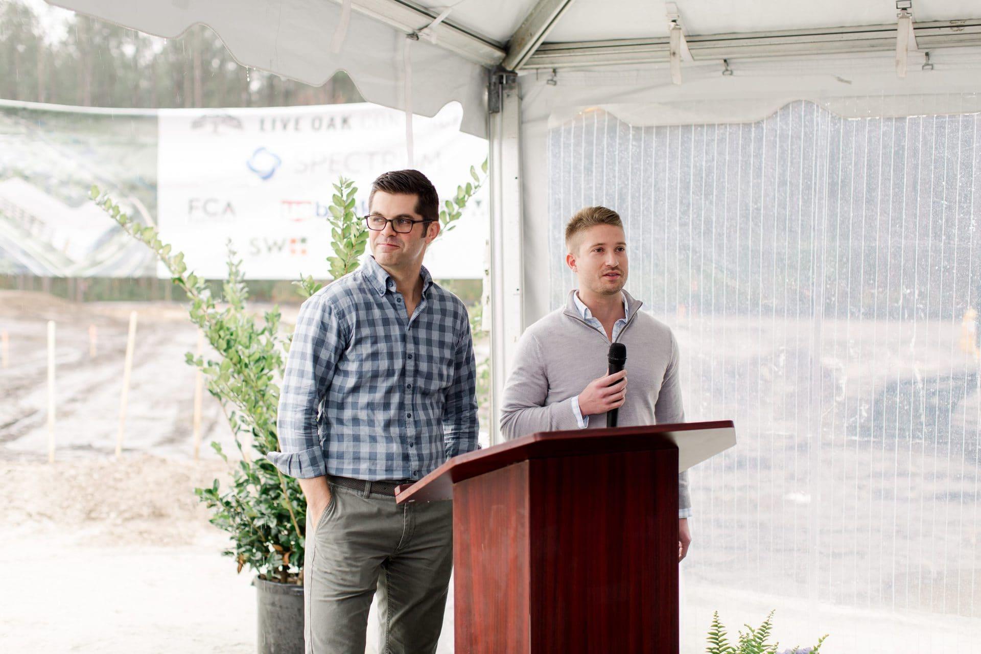 two men speaking at podium