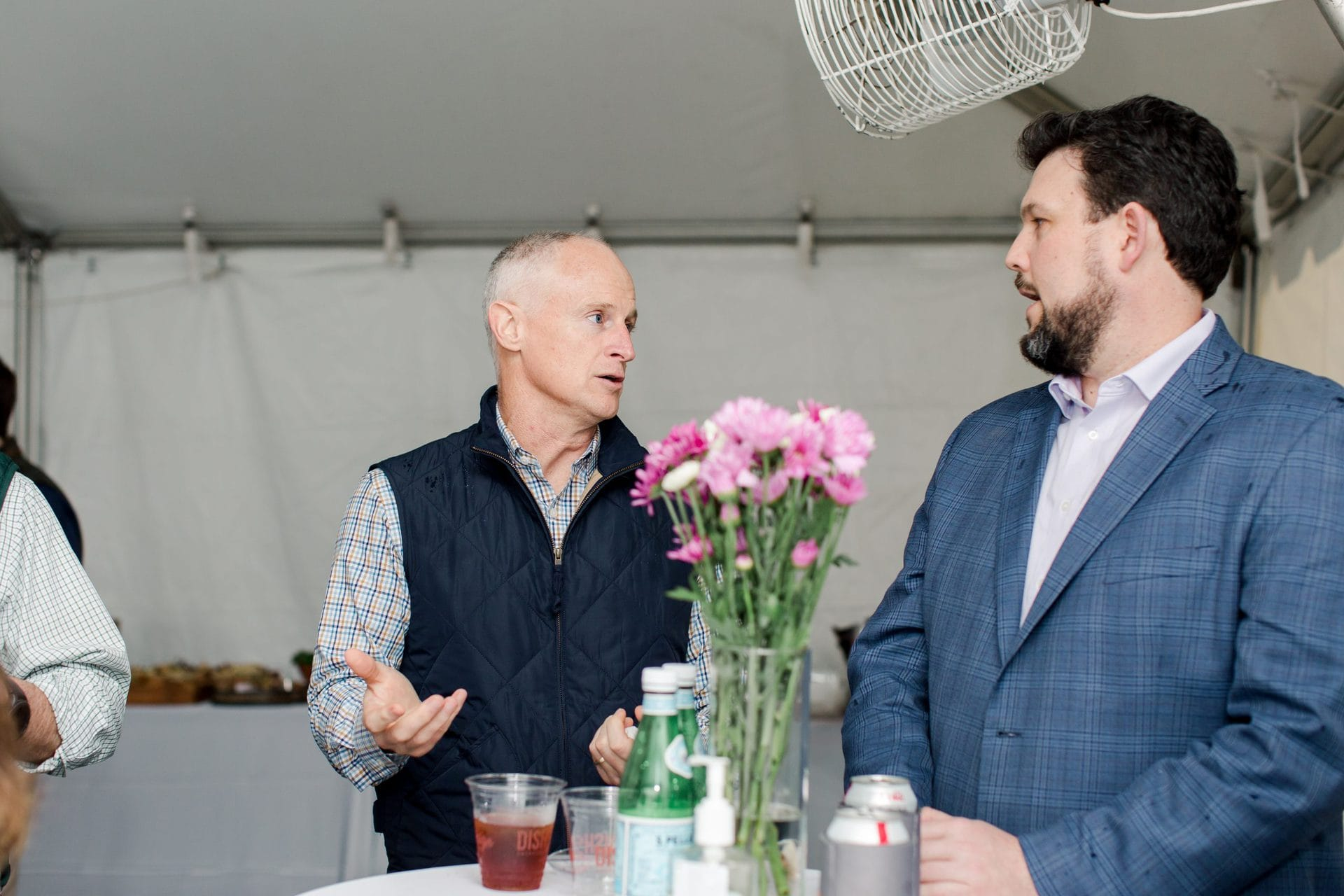 two men speaking at event