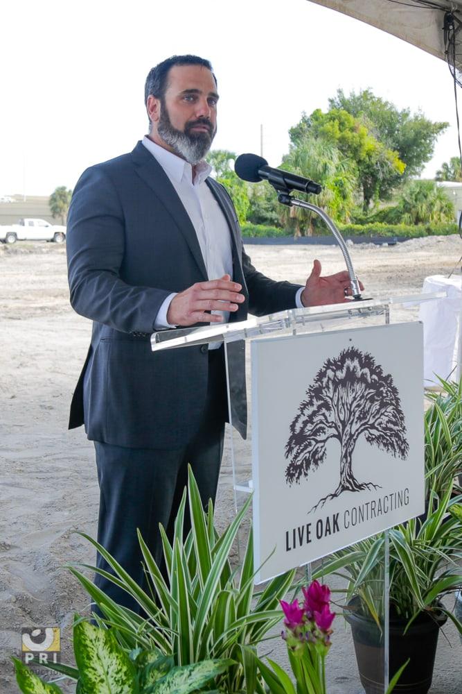 man at podium speaking outside