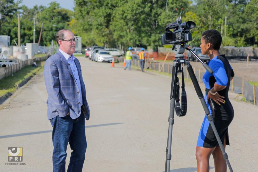 newswoman interviewing man at constructions site